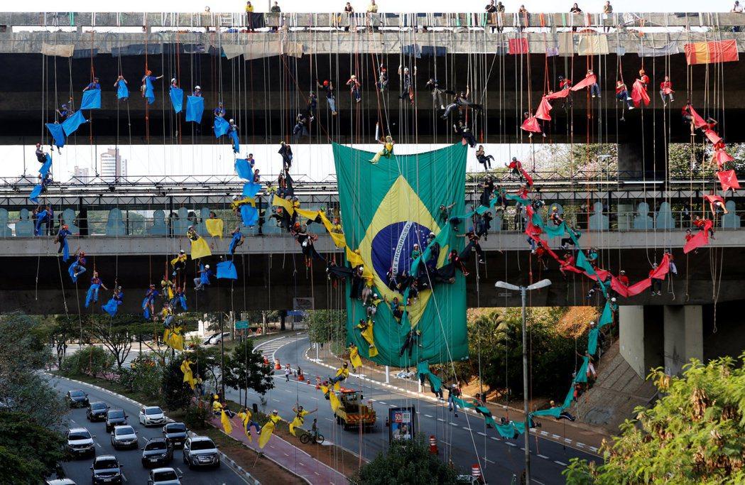 巴西聖保羅的一道橋上,有民眾掛起國旗,並身披彩布組成奧運五環圖案。 圖/路透