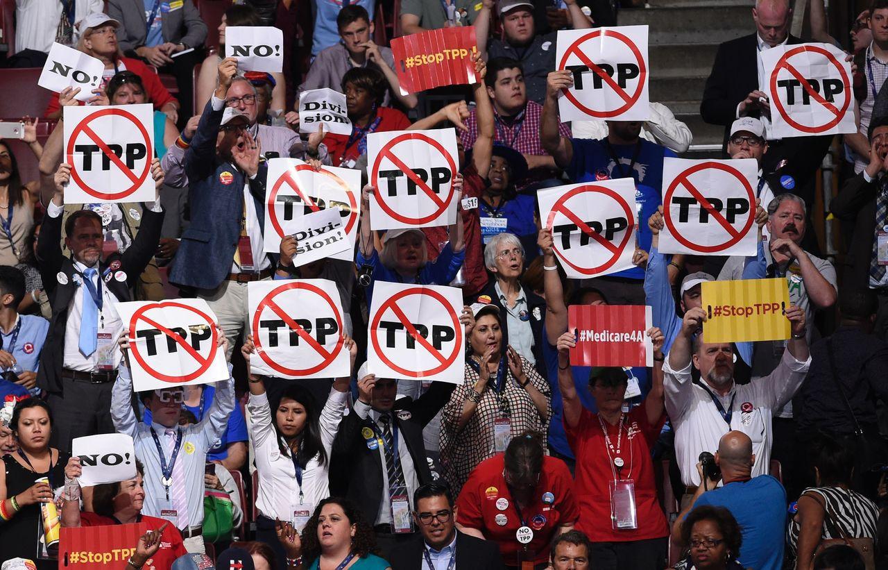 美國民主黨在費城的全代會提名希拉蕊參選總統,許多民眾高舉反對TPP的標語;希拉蕊...