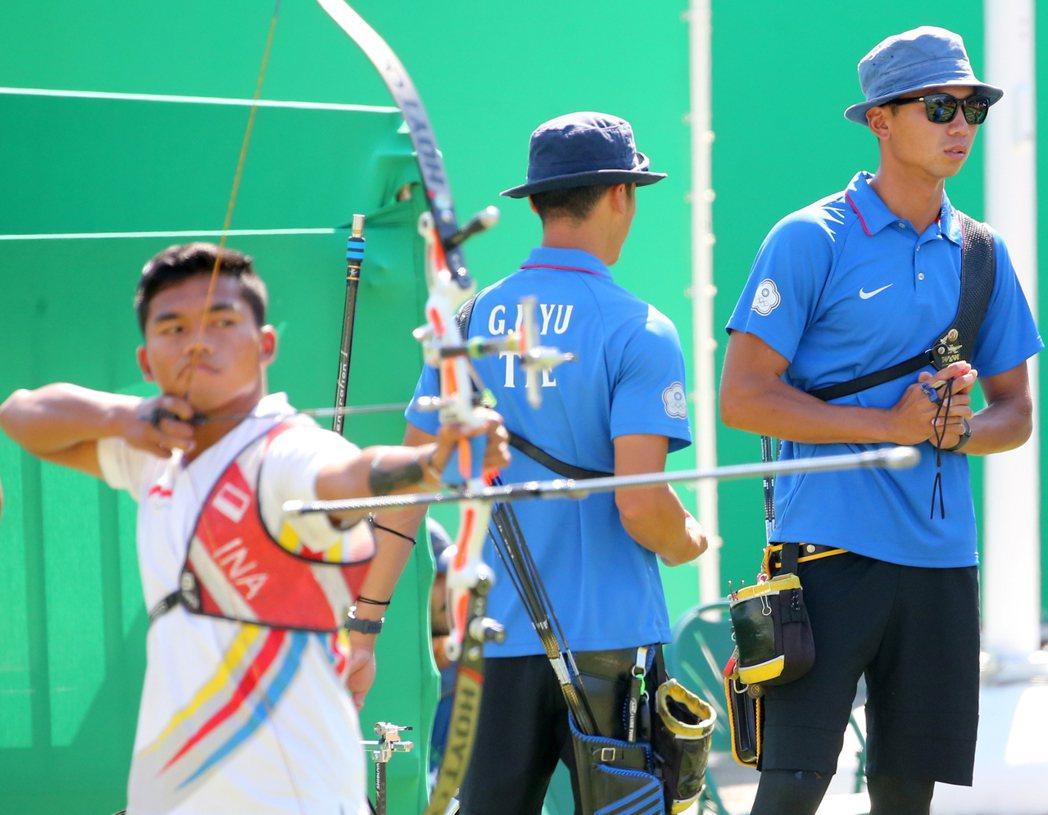 中華男子射箭團體站昨天舉行,對上印尼隊不幸敗陣,隊員魏均珩(右)在印尼隊射箭時,...
