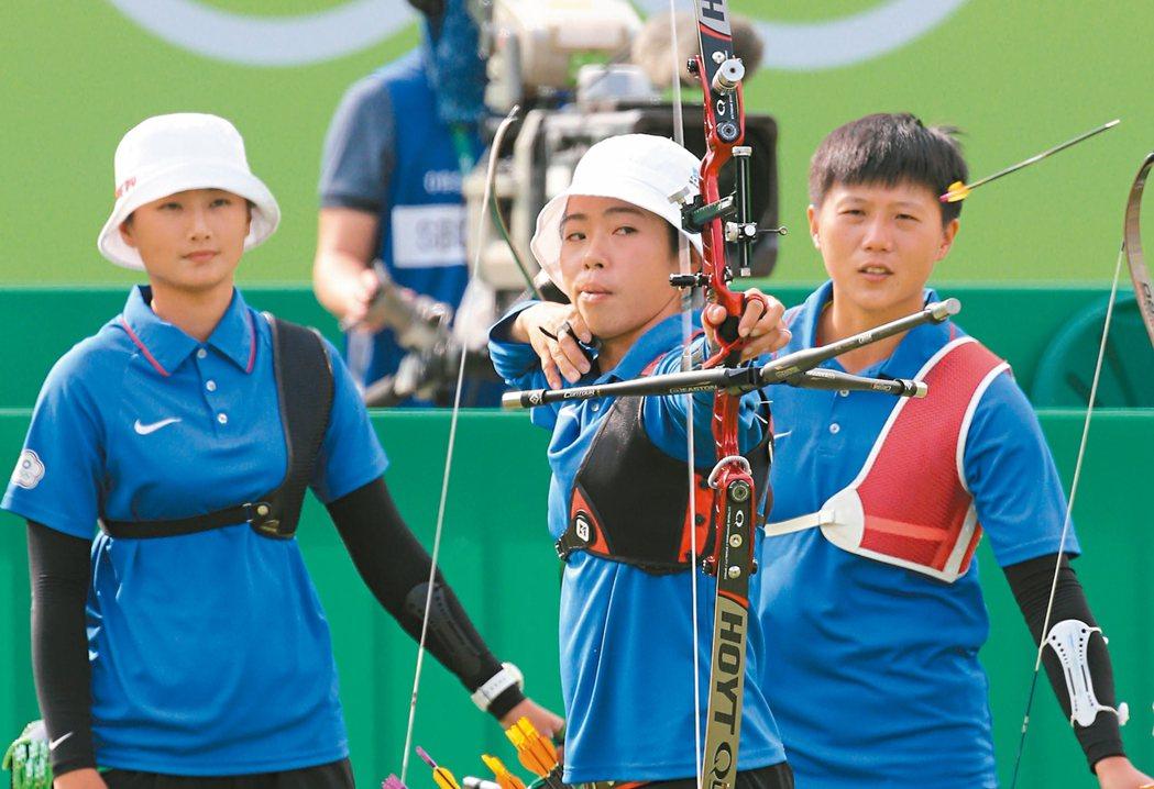 中華射箭女將譚雅婷(中)放箭,隊友雷千瑩(右)、林詩嘉(左)在後觀看,三人合力在...