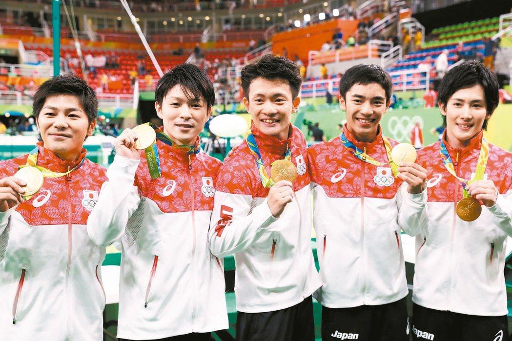 日本體操名將內村航平(左二)領軍贏得男子團體賽金牌。 歐新社