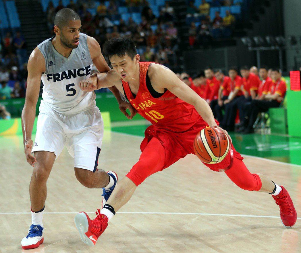 中國球員周鵬(右)設法突破法國防守。 新華社