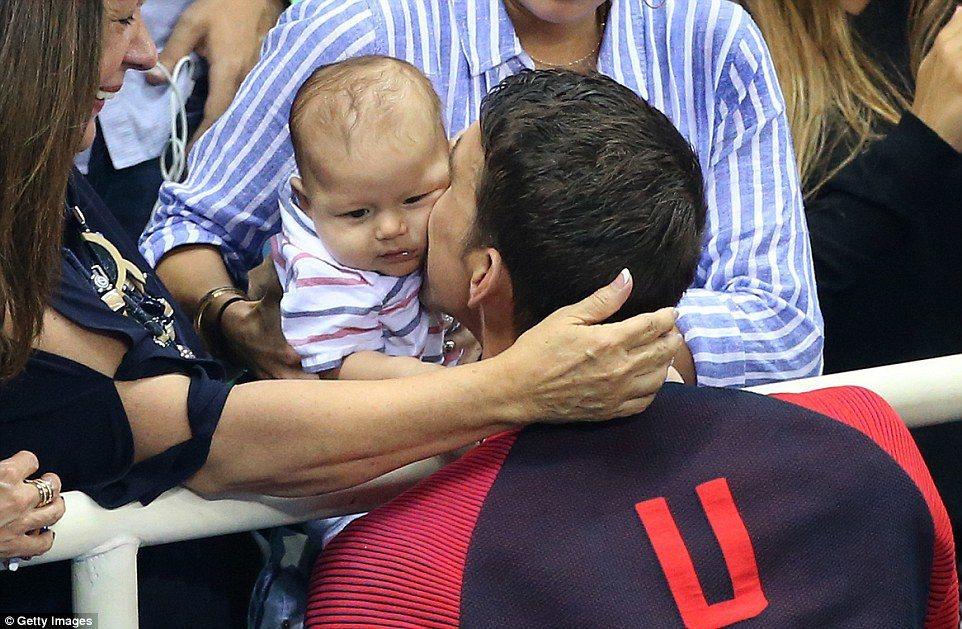 三個月大的布默,被奧運天王菲爾普斯在游泳池畔親吻。美聯社