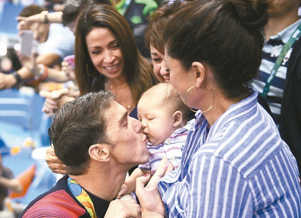 飛魚奪金後吻三個月大的兒子。 法新社