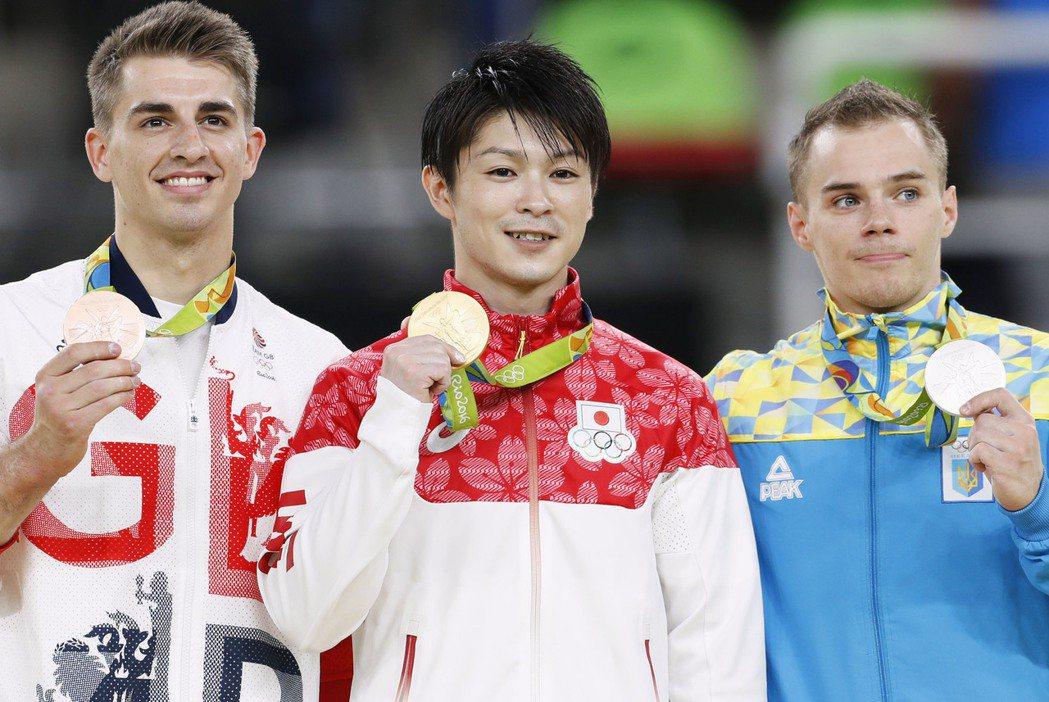 日本體操巨星內村航平(圖中)10日開心拿著里約奧運男子個人全能項目金牌,與鍍銀的...