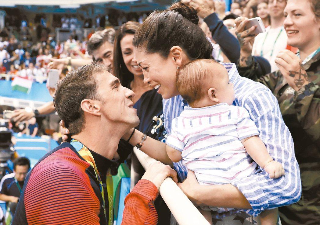 菲爾普斯(左)贏得金牌,總會走向妻兒,一起祝賀。 美聯社