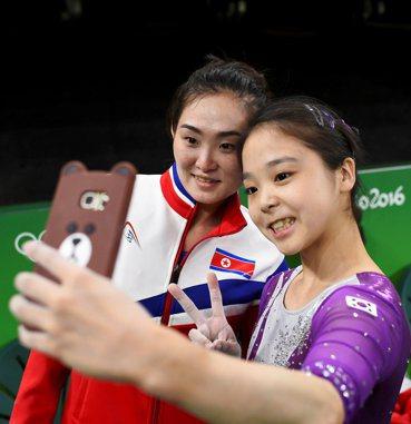 南韓體操選手李恩珠(左)和北韓選手洪恩貞4日在里約奧運賽場邊一起自拍。(路透)...