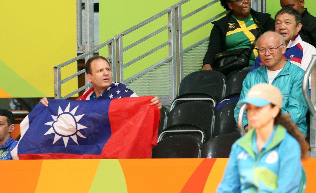 (圖一)來自美國的克里斯晚上再度帶著國旗與國旗裝在羽球會場幫周天成加油,害怕被阻...