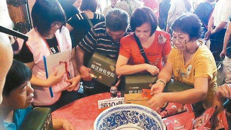 彰化縣在地特色產業結合傳統民俗,昨天舉辦博餅大賽,民眾專注擲骰子,希望多贏一些獎...