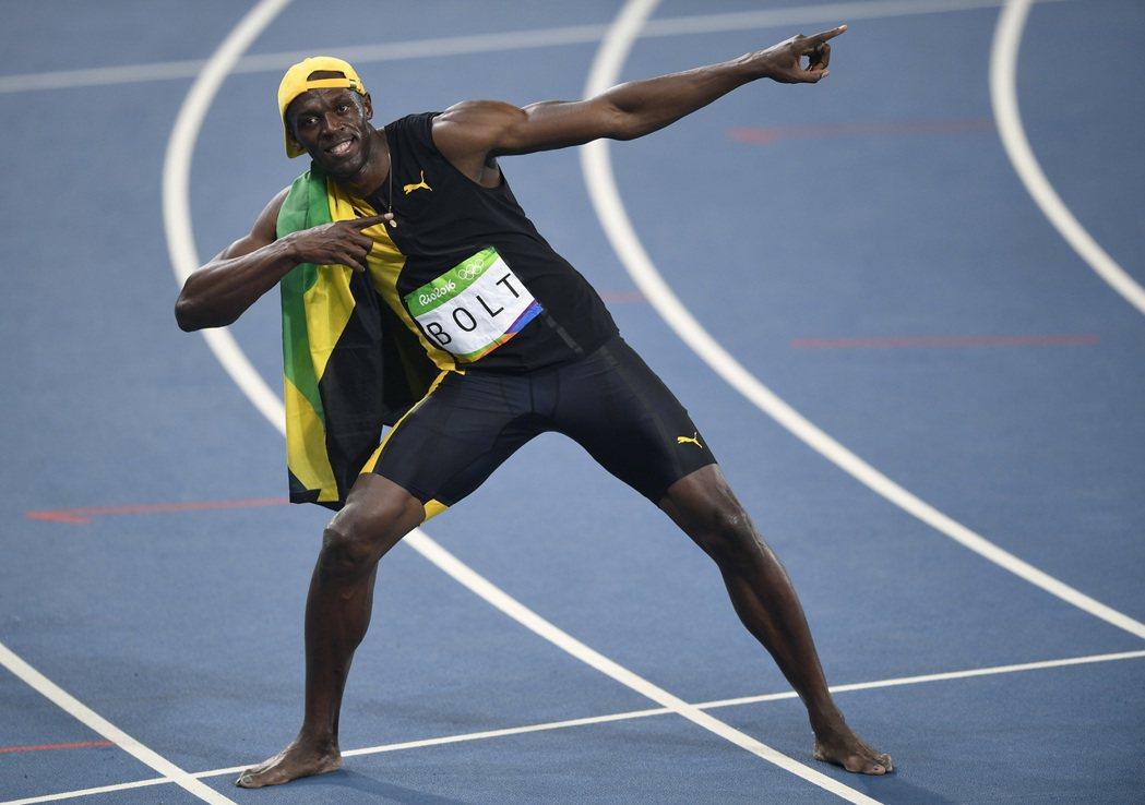 柏特贏得百米金牌後,披著牙買加國旗拉弓。 美聯社