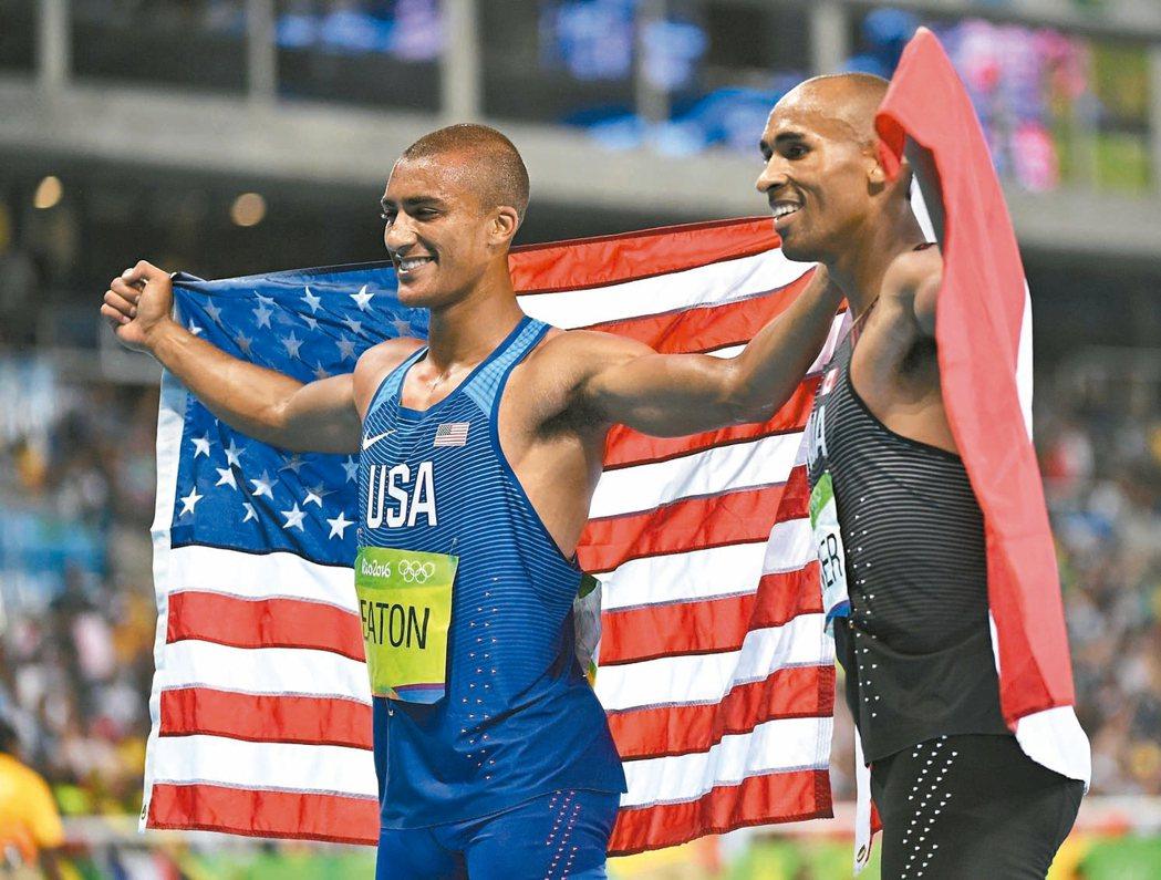 美國伊頓(左)及加拿大華納興奮披國旗慶賀奪牌,兩人在男子十項分獲金、銅牌。 歐新...