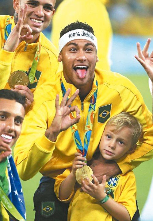 巴西足球明星內馬爾助隊贏得第一面奧運男足金牌,興奮抱著兒子。 歐新社