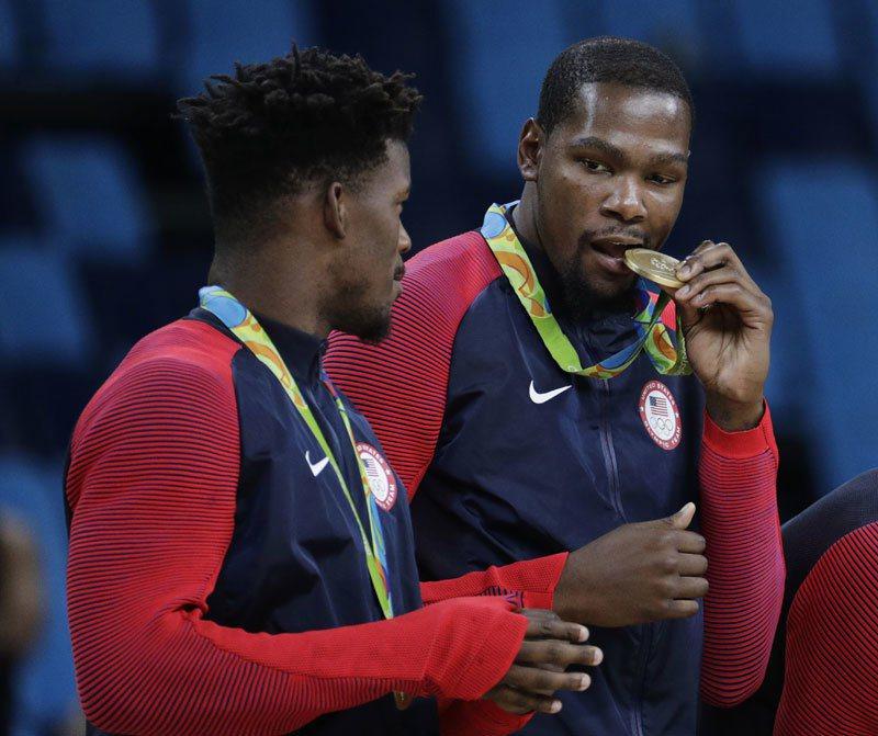 美國男籃奪得里約奧運冠軍,杜蘭特(右)嘴咬金牌慶祝。 美聯社