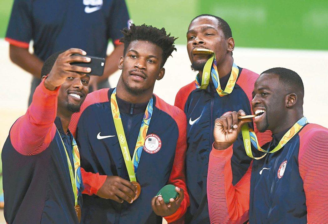 美國男籃隊在奧運摘金,選手快樂自拍,杜蘭特(右二)及格林(右)都咬著金牌。 路透