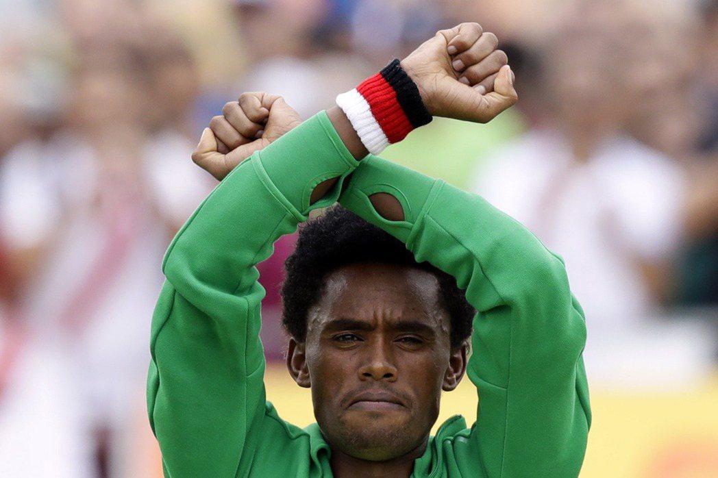 里約奧運馬拉松選手利勒沙(Feyisa Lilesa)在衝破馬拉松比賽終點線時擺...