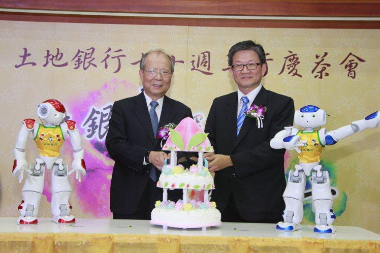 土地銀行董事長吳當傑(右)、總經理高明賢(左)與機器人土銀哥、土銀妹一起切蛋糕,...