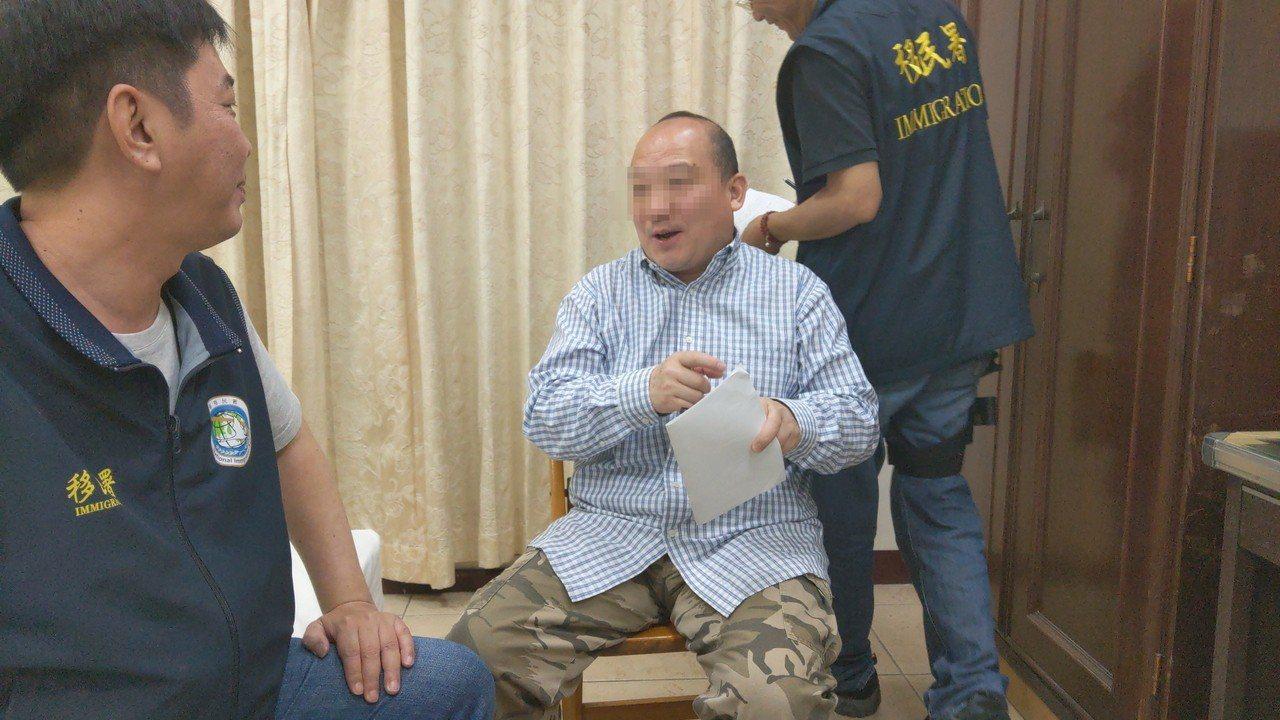 移民署人员对李毅(中)开立处分书,废止李一年多次入台证,李毅签名时频说,「我马上...