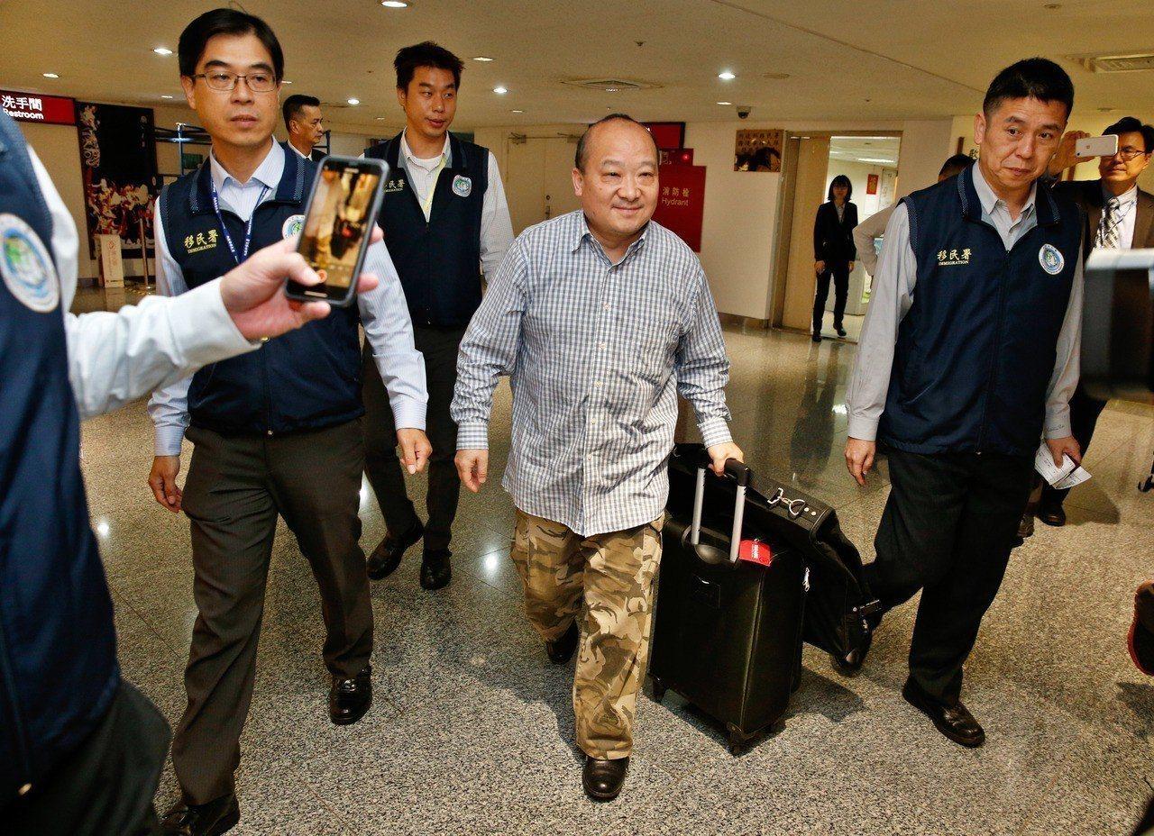 旅美大陆地区的武统学者李毅(中)上午遭移民署强制出境,在多名移民署人员戒护下前往...