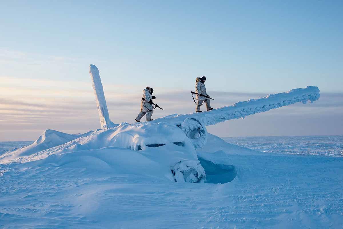 加拿大士兵爬上一架飞机的残骸侦查这个区域,地点在北极点以南约1600公里的康瓦力...