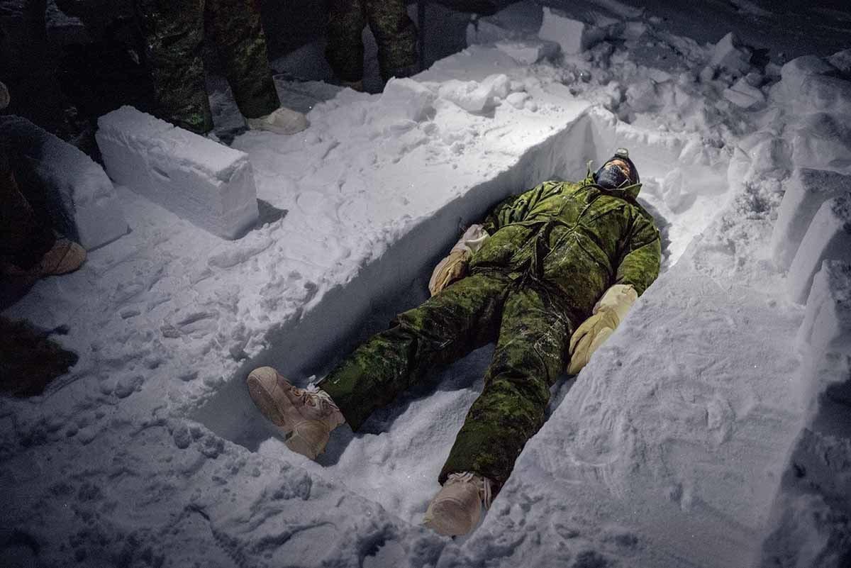 加拿大飞行员西蒙.金恩躺在自己挖的战斗壕沟中,那是他把冰一块块凿切出来所形成的。...