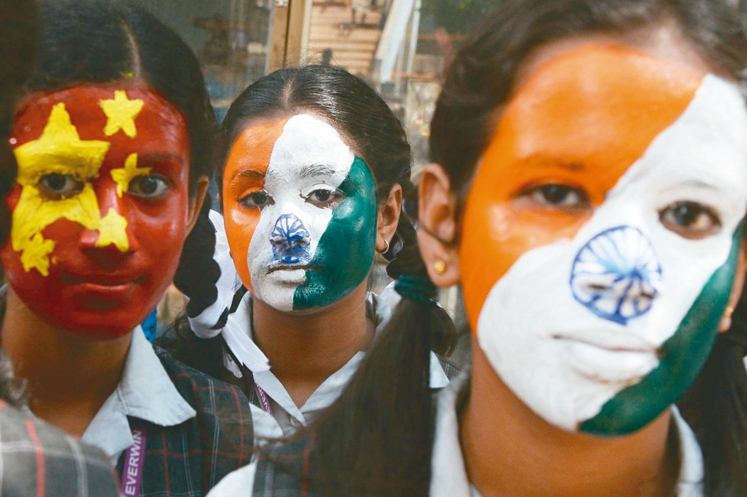 为欢迎大陆国家主席习近平,印度学童在脸上彩绘中印两国国旗。 (法新社)