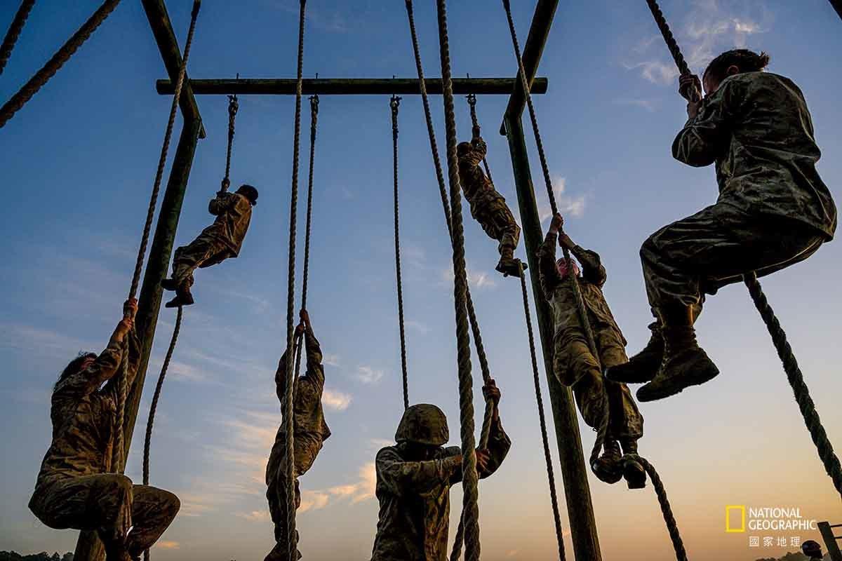 【美国】 帕里斯岛的陆战队女新兵在攀绳时高声鼓励彼此。她们得靠极少的口粮与睡眠撑...