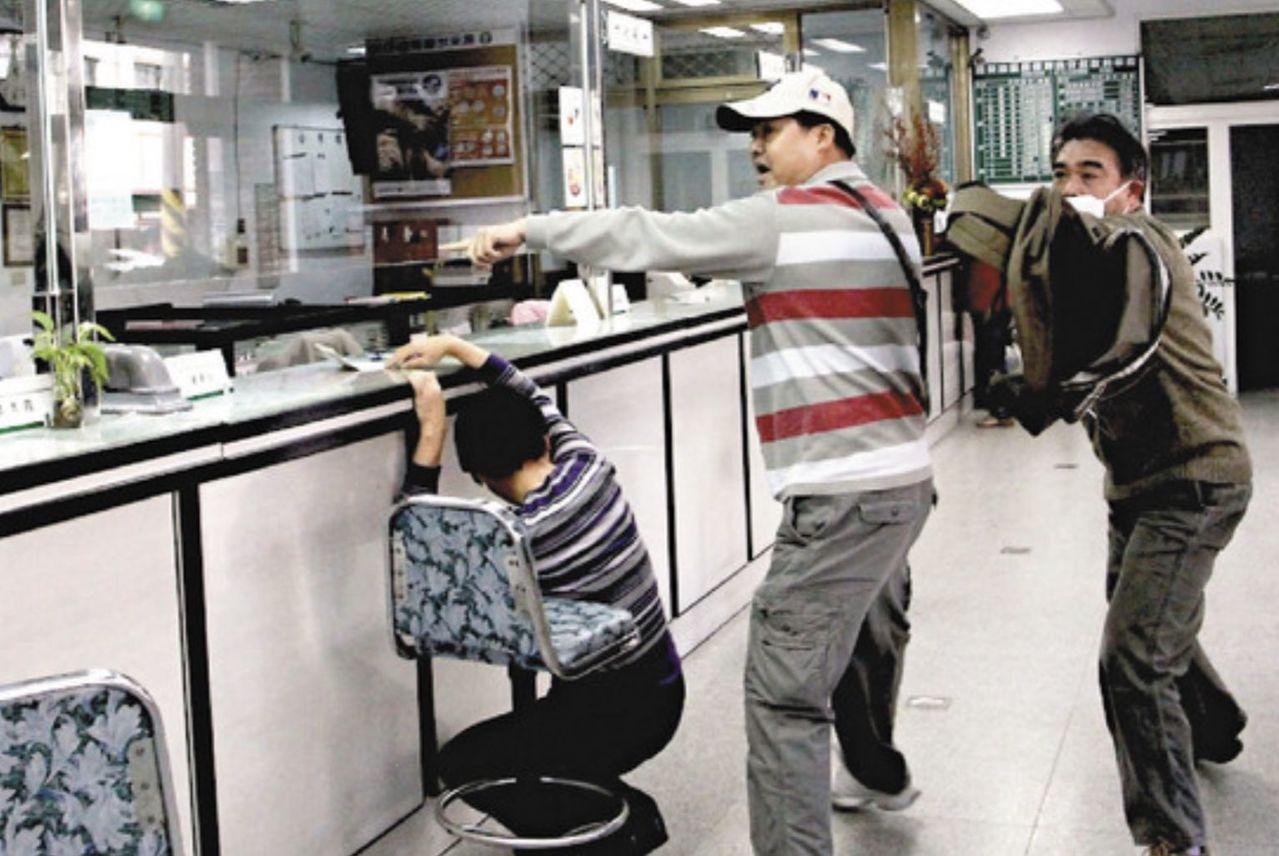 假歹徒持枪不断朝柜台比划。图/联合报系资料照片