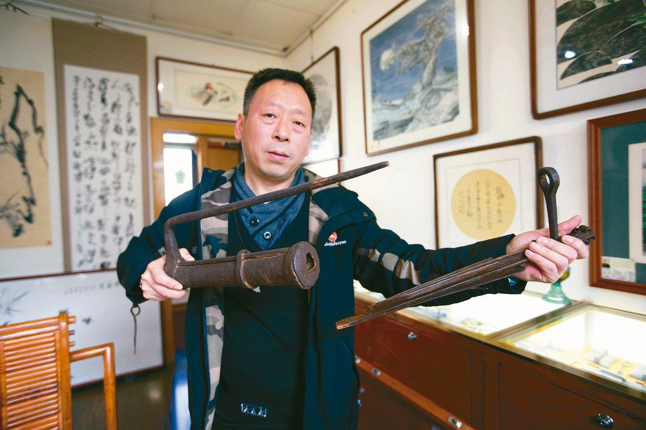 图为孟卫平展示自己收藏的古锁。 中新社