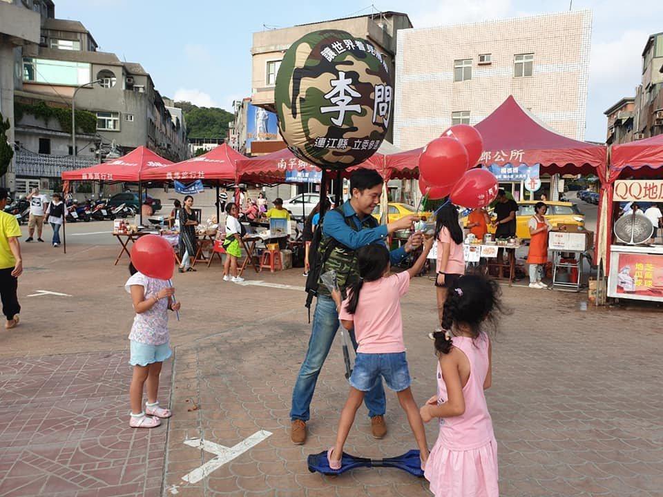 民进党连江县立委参选人李问,利用行动式背包气球及发送气球方式宣传政见。 图/截自...