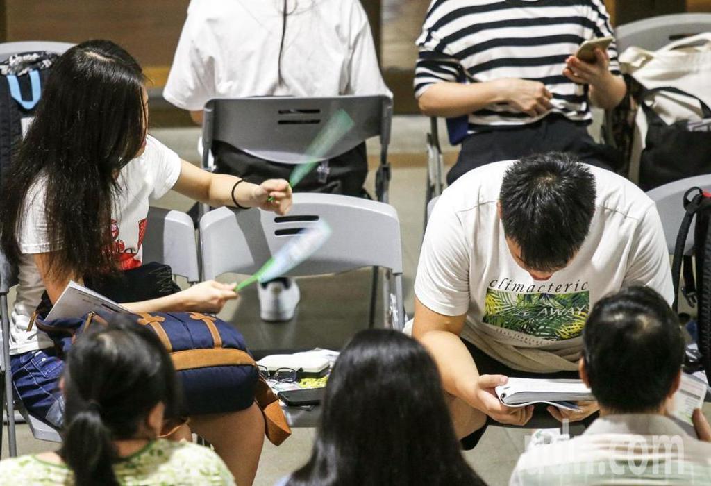 大學指考進行第2天的考試,共同科目、數乙及數甲考試登場,全部約5萬多名考生上午一起應考,陪考的親友使出手搖雙扇,讓考生能稍解悶熱。