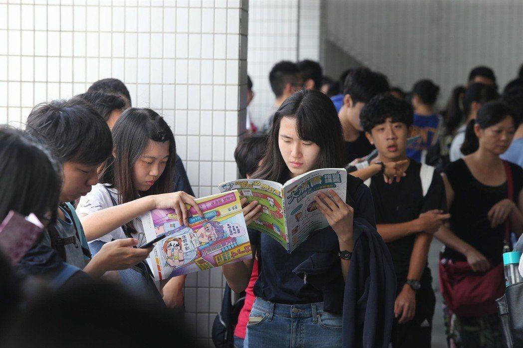 107學年度指定科目考試2日進入第2天,考生在教室外翻閱參考書,準備第一科的考試。