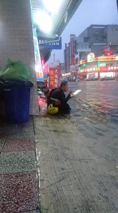 南台灣淹大水,警義消救災忙翻,得空坐路旁用餐。