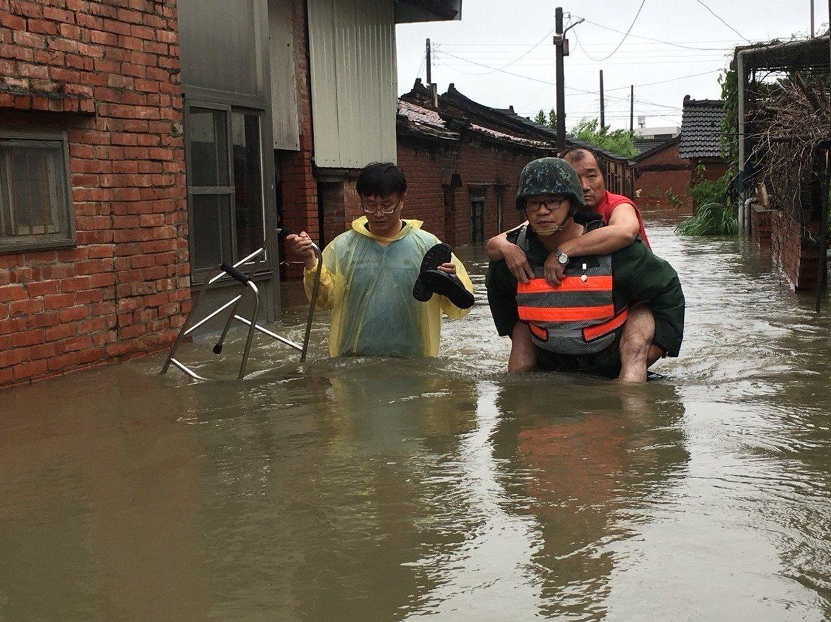 嘉義布袋東石沿海巷弄全淹水,官兵在大水中背著受困民眾走出淹水家園。