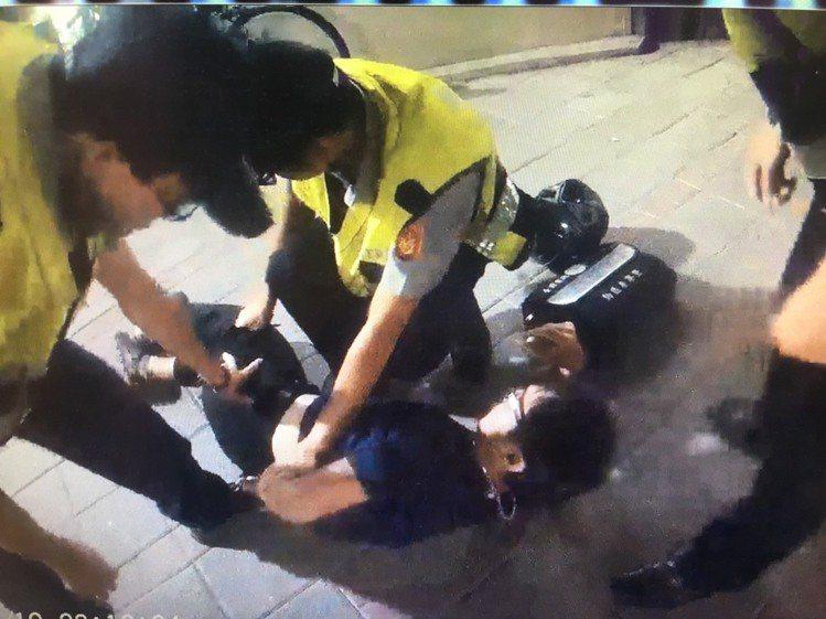警方圍捕鄭姓通緝犯,把他壓制在地方盤查身分。記者林昭彰/翻攝