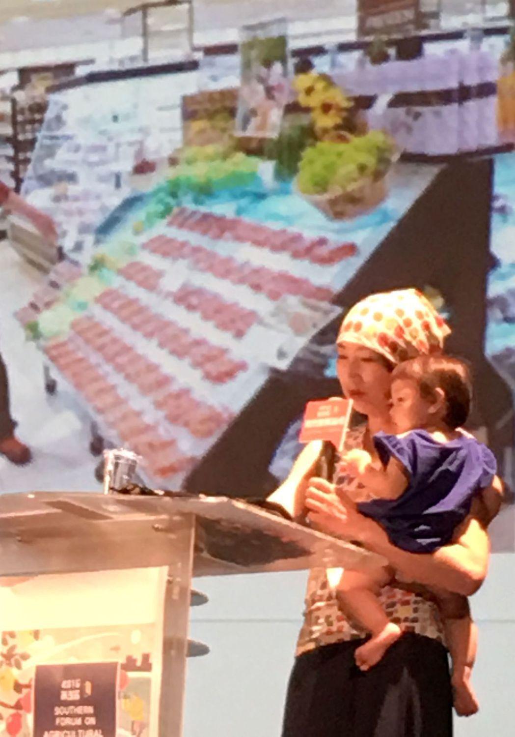 日本山形女子農場社長高橋菜穗子參加第三屆南方農業論壇,她抱著女兒上台演講,強調用...