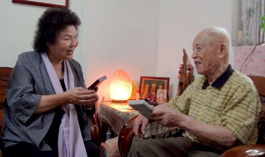 高雄市101歲人瑞磨震彪(右)喜歡用掌上型遊戲機打俄羅斯方塊來訓練腦力,高雄市長...
