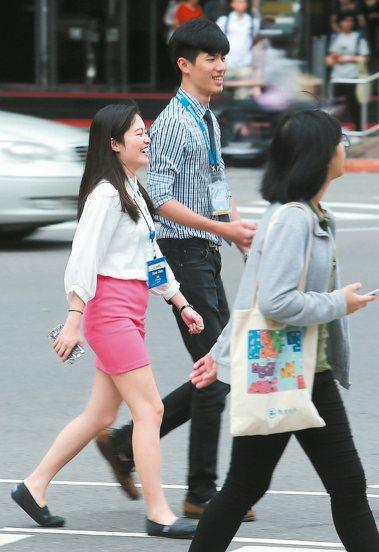 根據人力銀行調查,逾七成七上班族有意前往海外工作,圖為街頭的年輕上班族。 報系資...