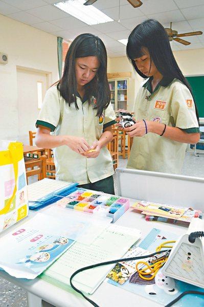 一有空檔,學生們抓緊時間「做手工」。 記者施鴻基/攝影