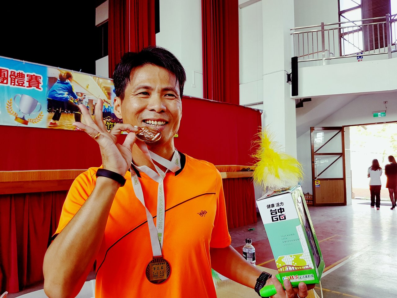 廣興國小校長陳鐘金參加踢毽比賽奪金,開心咬著金牌。記者吳佩旻/攝影