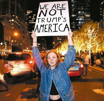紐約聯合廣場一名女子在川普看板寫字發洩不滿;在費城,一名女子高舉「我們不是川普的...