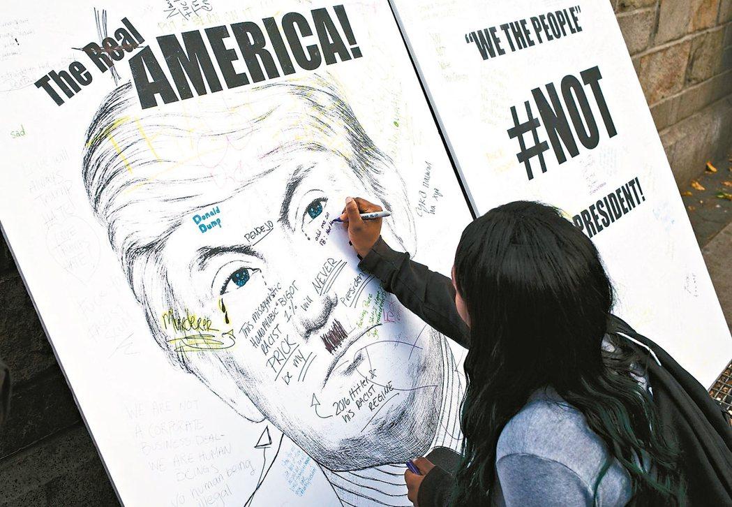 紐約聯合廣場一名女子在川普看板寫字發洩不滿(見圖);在費城,一名女子高舉「我們不...