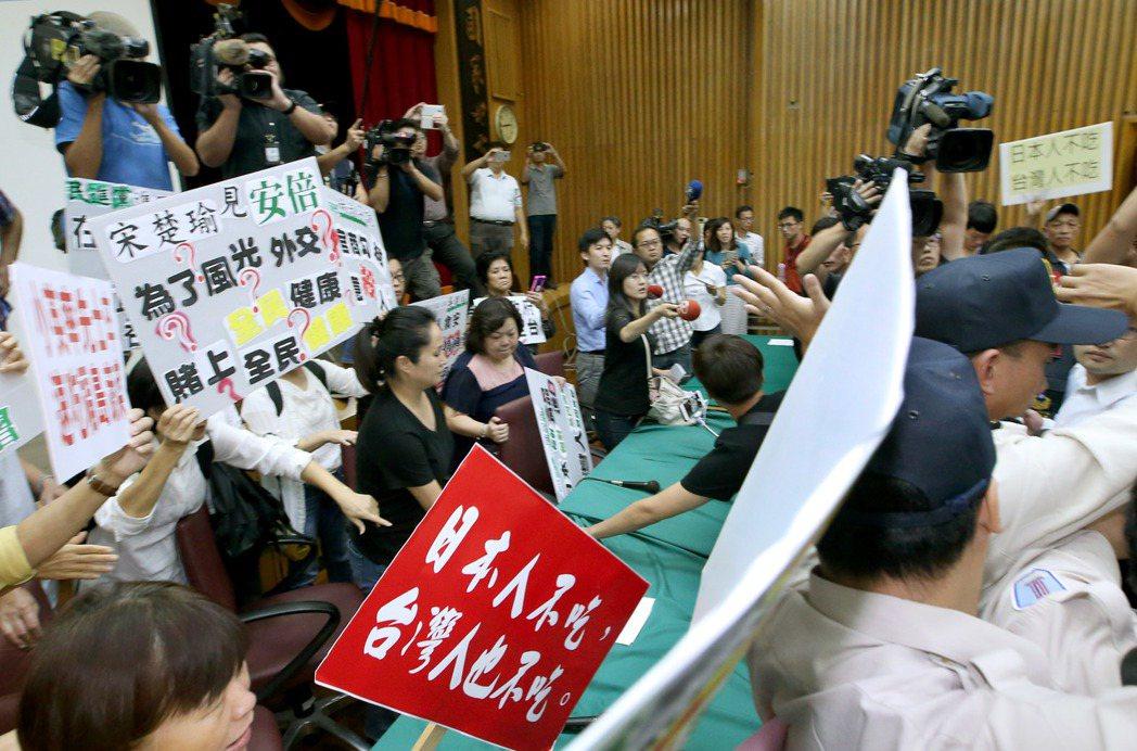 日本食品輸台公聽會台北場昨天在農糧署舉行,會議沒開始就大亂,藍營民代與民眾現場抗...