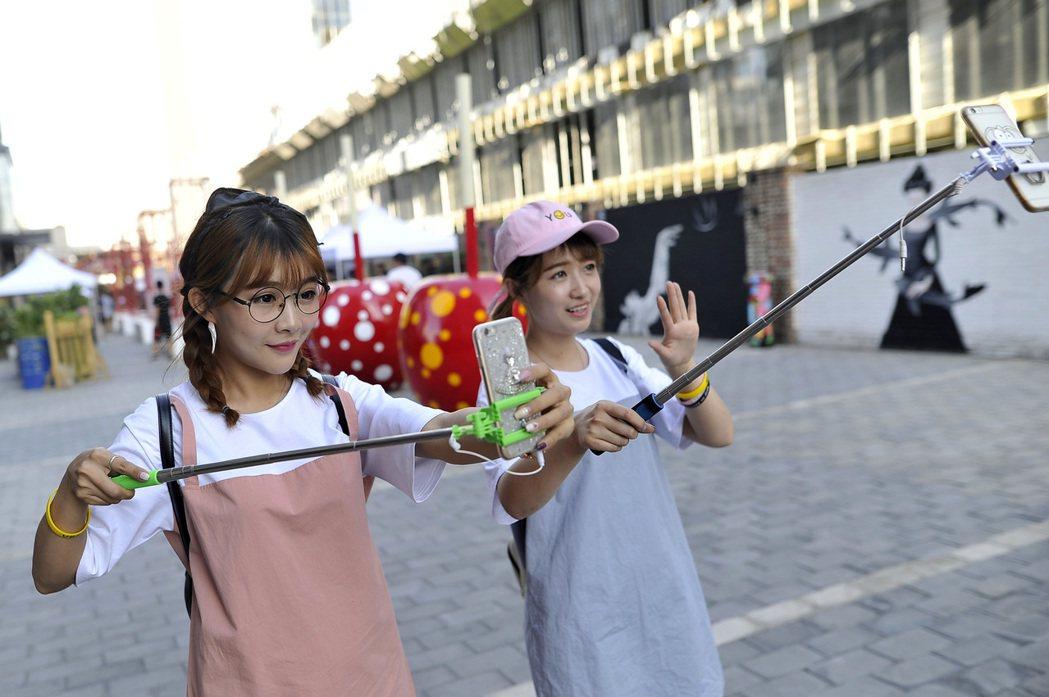 兩名女孩利用手機直播青年創意市集活動現場。中新社