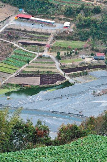 萬大水庫的上游塔羅灣溪淤積嚴重,昔日深峻的溪谷堆滿了土石,快要淹沒農地。 記者邱...