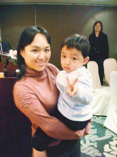 「小亨利」在媽媽懷裡比出勝利手勢,似乎忘了2年前又吐又拉的不舒服。(記者詹建富/...
