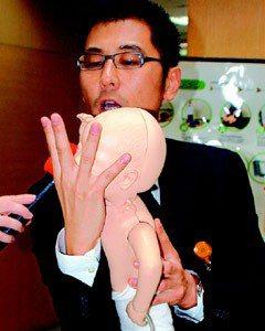 醫師賈蔚示範嬰兒哈姆立克急救法。步驟1:用手扶住臉部,準備倒置。(記者賈寶楠/攝...