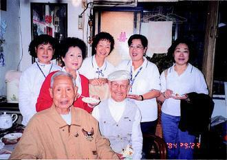 彭媽媽(身穿紅外套者)每周都會前往老人中心服務,餵老人吃東西,逗老人開心。(圖片...