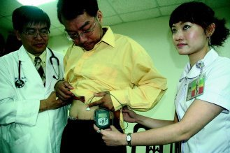 圖為1名透過「連續血糖監測器」追蹤血糖變化的患者。(圖/記者蔡維斌攝影)