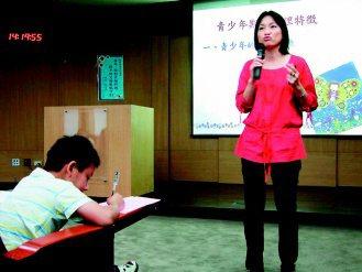 淡江大學教授柯志恩專題演講如何面對狂飆期的孩子,有小朋友陪家長聽講,並利用時間畫...