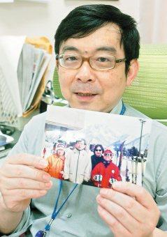 黃立民醫師拿著全家福照片,談起全家養生經,不禁露出幸福的笑容。(記者陳柏亨/攝影...